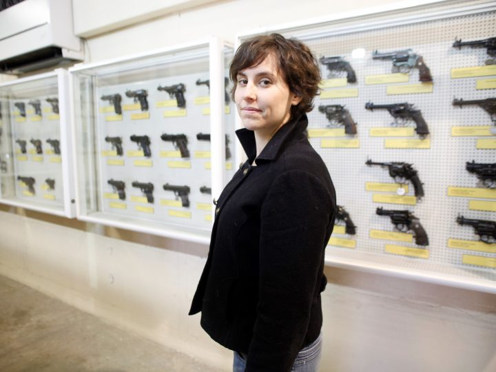 portrait of the artist in front of a case of guns