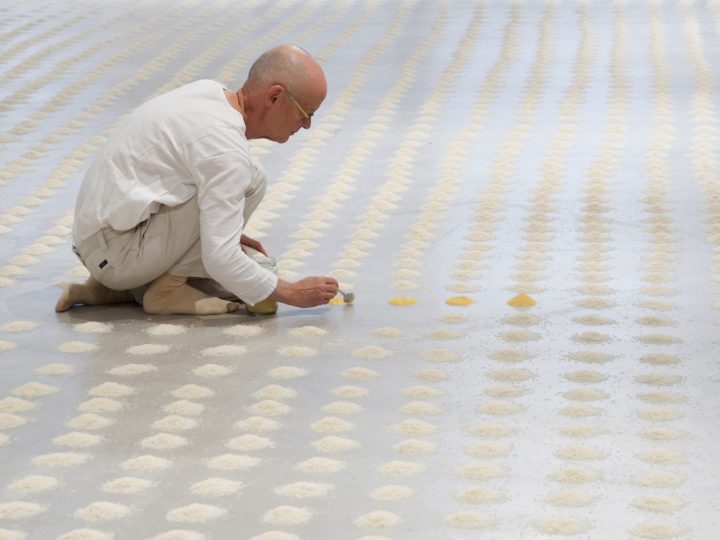 image of a man sat down surrounded by small piles of rice in circles, placing a small circle of pollen down with a spoon