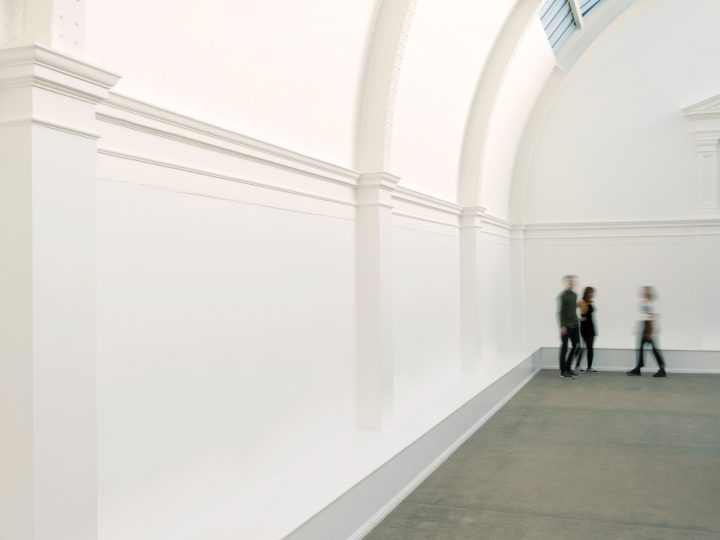 image of a white room with a curved ceiling with 3 blurred figures