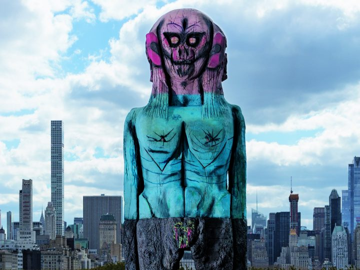 image of a large purple and blue human sculpture in front of a city skyline
