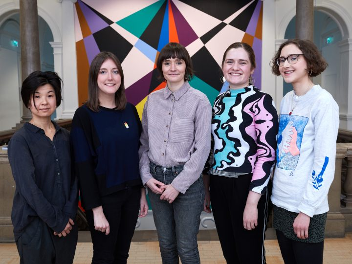 A group of five women stand in front of a colourful wall painting