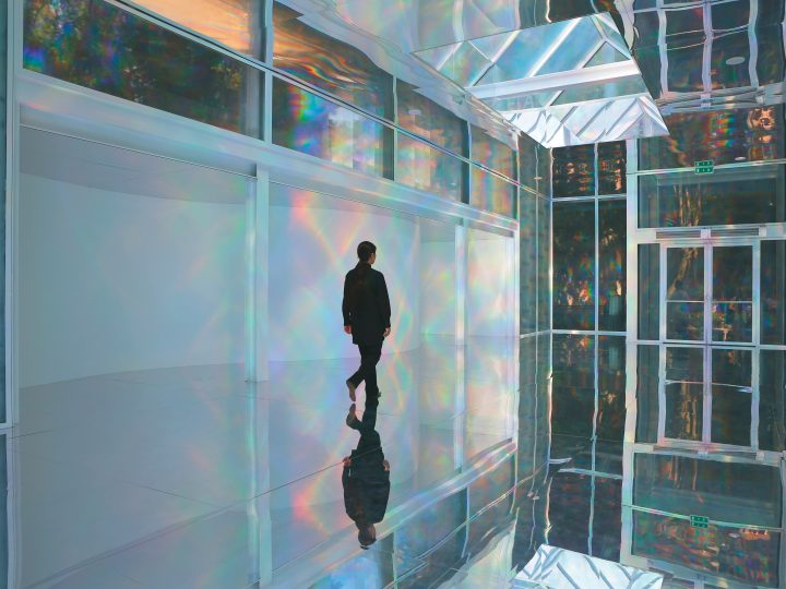 image of a gallery space with mirrors and rainbow light reflections