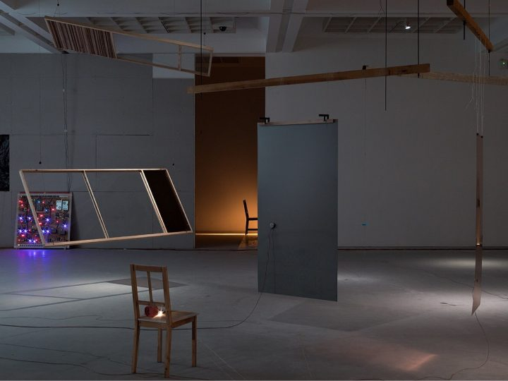 image of a gallery space featuring a piece of work with suspending shapes from the ceiling and a door in the middle of the room.