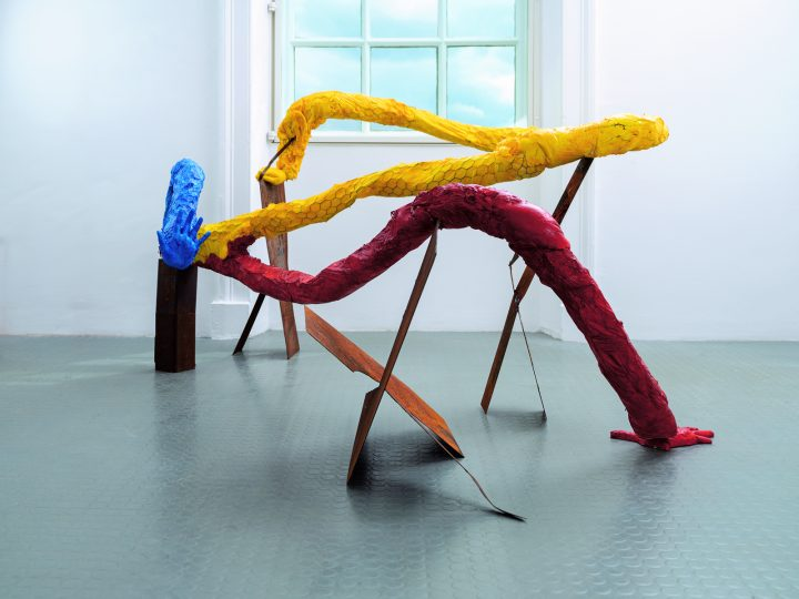 This sculpture consists of blue, yellow and red tube like sculptures with hands at the end. They curl and twist upwards from the floor and are supported by pieces of rusted metal.