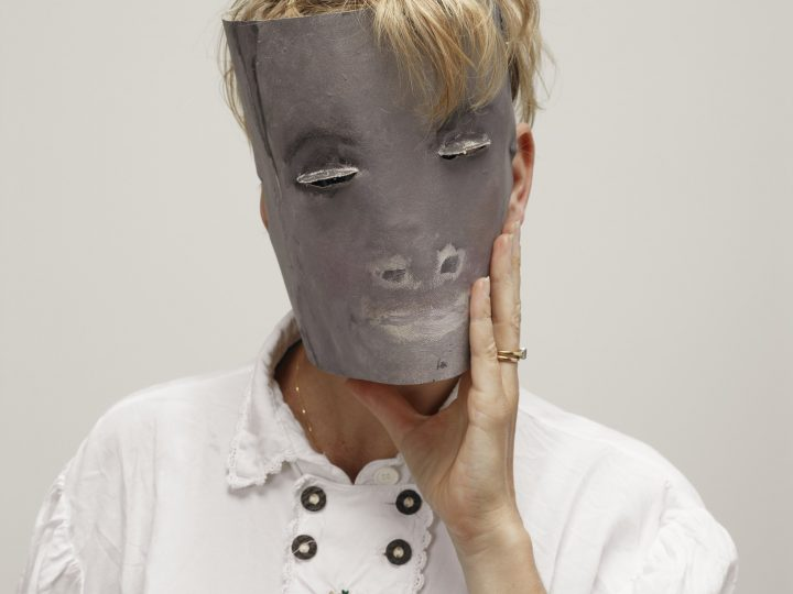 Artist Laure Prouvost is photographed with a paper mask covering her face. The mask is gray with painted features including nose, mouth and eyes which are small slits. She wears a white shirt and has blonde hair.