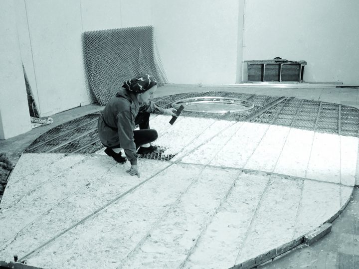 Black and white image of a woman (Barbara Hepworth) crouching on the ground whilst working on a large flat sculpture.