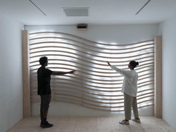 A man and woman stood in front of a sculpture with light emitting from behind wavy wooden slats.