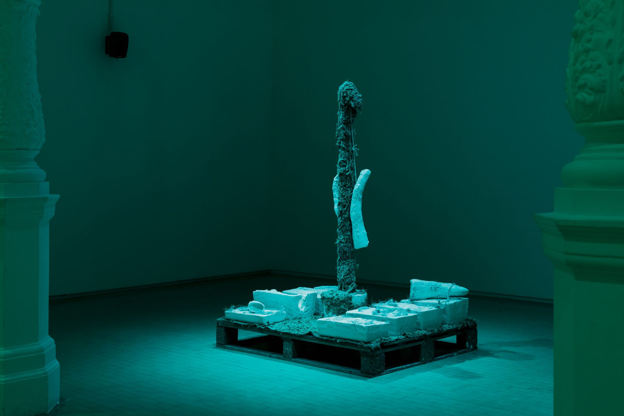 A mixed material sculpture by Ashley Holmes in the middle of a room, bathed in blue light.