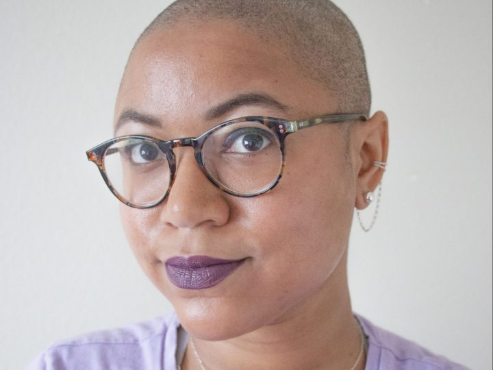 Black American with a clean head shave. They are wearing a purple shirt and a silver necklace of a tree. Also they are wearing round brown and black glasses and burgundy lipstick.