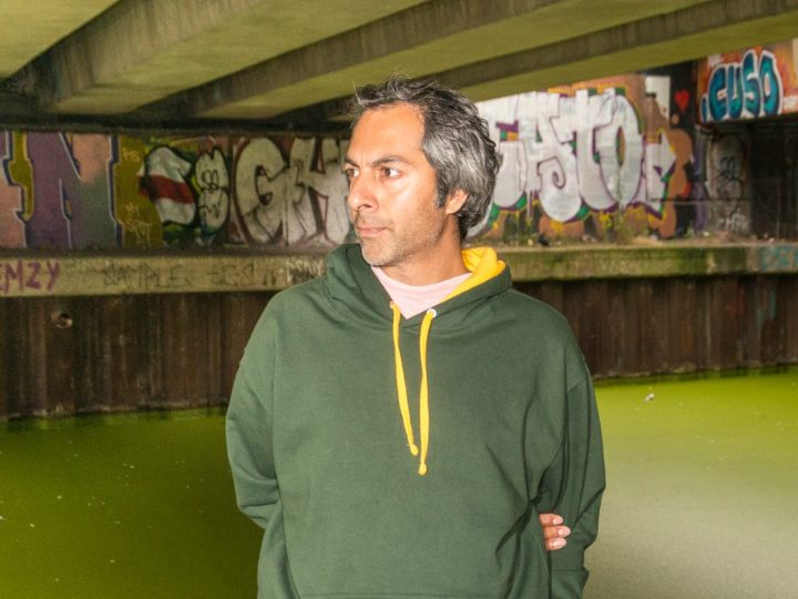Portrait of British artist Shezad Dawood. Shezad Dawood stands under a bridge against a London canal. He is looking to his right and wearing a dark green hoodie with a front central pocket, with a yellow hood with yellow pull ties. A pale pink t-shirt is visible at the collar and coming out from under his sweatshirt. He holds his right arm behind his back. His left hand is in his left pocket. The water behind him is covered in lime-green algae. The wall above the opposite bank is covered in multi-colour graffiti.