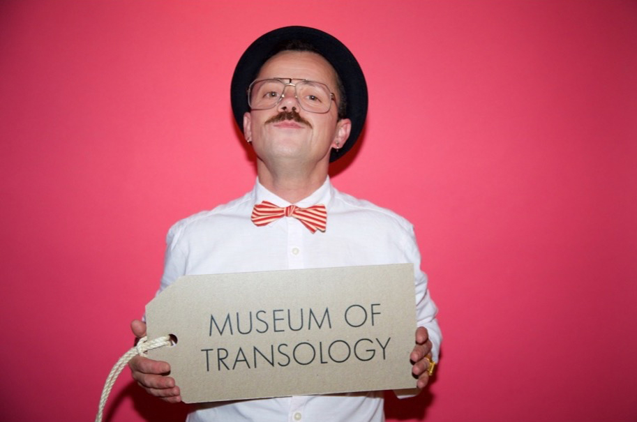 In this image, E-J is a masculine presenting trans man with a moustache and wears gold spectacles, a black trilby hat, a cream and pink striped bowtie and pink business shirt. He is solding up a large brown Museum of Transology sign that is an oversized version of the tags that are attached to the objects in the MoT collection.