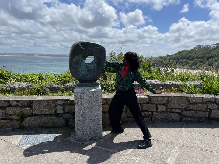 A woman (Nwando) poses next to a Barbara Hepworth sculpture on a sunny day near the sea.
