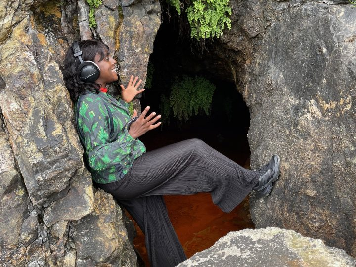 Nwando stands between rocks with one foot up, wearing headphones and smiling.