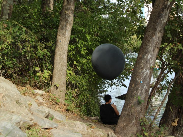 Black American facing away from the camera and laying horizontally on a rock positioned on the bottom right of the image. They are dressed in all Black with their feet and arms exposed as they hold a Black Weather Balloon above themselves. They are sitting along the bank of a river with high mountains.